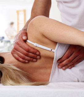 This image shows a woman laying on a table. There are hands on her shoulder blade, part of full body chiropractic adjustments.